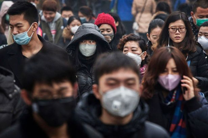 Chinese commuters many wearing masks walk to work during heavy pollution.jpg?ixlib=rails 2.1
